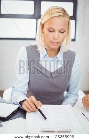 Businesswoman reading documents while sitting at desk in office