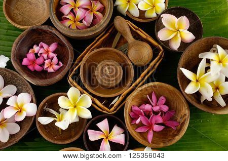 Spa setting Background with frangipani in bowl with green banana leaf