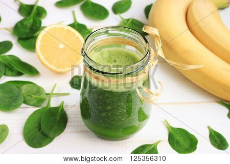 Green spinach and banana smoothie benefits. Green smoothie drink in glass jar, fresh fruit scattered white table. Summery refreshing drink