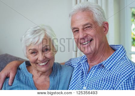 Close-up portrait of smiling retired couple with arm around at home