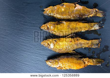 top view of fried tench fish served on slate background close up