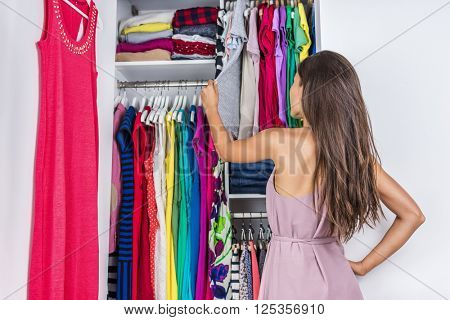 Home woman choosing her fashion outfit in dressing room. Woman in bedroom walk-in organized closet looking at clothes hanging deciding what shirt to wear in the morning. Shopping store clothing rack.