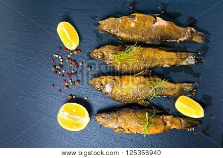 top view of fried tench fish served with aromatic rosemary lemon and dry peppers on slate background close up