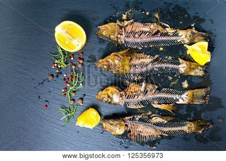 top view of fish skeleton bones squeezed lemon and flavor peppers on slate background close up