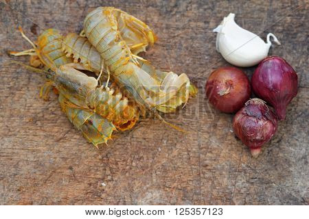 Silver mantis shrimp or known as udang ketak and udang lipan in Malaysia with small onion and garlic on old wooden chopping board. Shrimp ready to be cooked after mixed with turmeric and salt.
