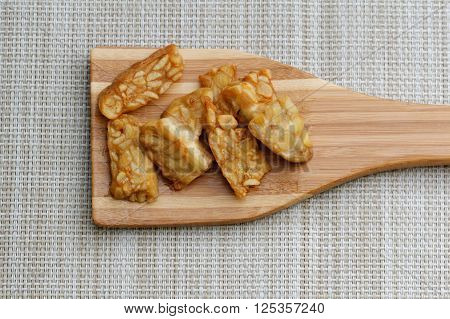 Fried Tempeh in wooden spatula on textured background. Tempeh is made from soy bean and popular in some part of Asia.