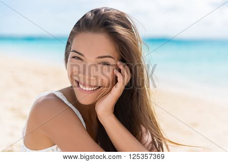 Healthy beautiful Asian multiracial woman on beach. Portrait of pretty Chinese Caucasian mixed race brunette girl in her 20s relaxing on summer vacations. Confident and modern young adult.