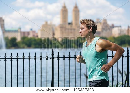 Male runner running in New York City Central Park during summer travel along the lake with view on skyscrapers background. New yorker living a healthy and fit lifestyle.