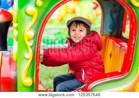 Beautiful Boy Having Fun On The Ride At The Amusement Park