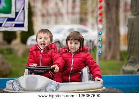 Two Boys, Riding Boat In Amusement Park