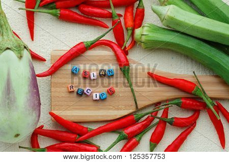 Eggplant or aubergine, chili, ladies' finger and one wooden spatula with alphabet block forming word ASIAN RECIPE arranged carefully and beautifully on textured background. View from above. Flat lay.