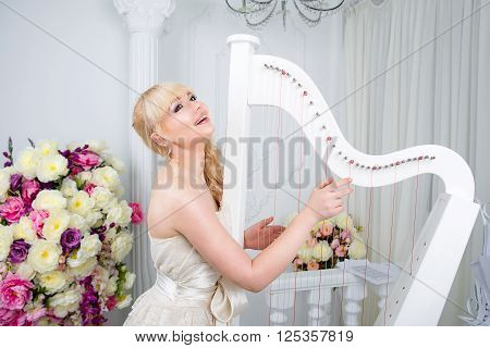 young beatiful blonde girl in long dress playing harp