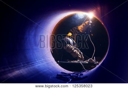 a worker performs welding of pipes on construction of the pipeline