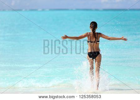 Freedom bikini woman running carefree with arms up swimming splashing water in ocean on tropical beach. Happy success girl from behind feeling free in summer Caribbean travel vacation.