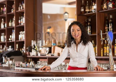 Pretty smiling Vietnamese bartender standing behind counter