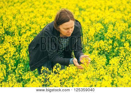 Agronomist woman examining oilseed rape flower blooming female agricultural expert in field of blooming rapeseed examining the growth of agricultural crops.