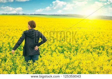 Woman agronomist standing in the field of blooming cultivated rapeseed plantation female agricultural expert controlling the growth of agricultural crops.