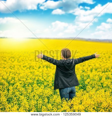 Woman agronomist standing in the field of blooming cultivated rapeseed plantation female agricultural expert controlling the growth of agricultural crops and looking to distant point on the horizon.