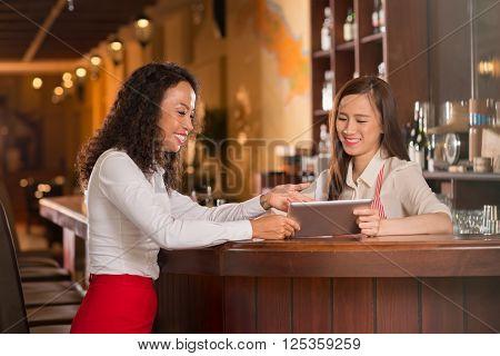 Bar manager showing waitress new menu on digital tablet