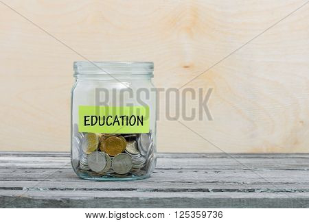 Label on a glass jar with the inscription - education. Glass jar with coins. Financial concept on wooden background