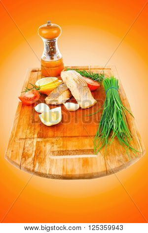 savory fish portion : grilled norwegian salmon fillet with green chinese onion, red cherry tomatoes , allspice pepper in grinder, rosemary twigs and lemon slice on wooden board
