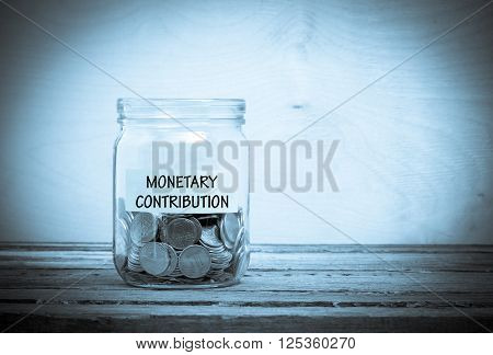 Label on a glass jar with the inscription - monetary contribution. Glass jar with coins. Financial concept on wooden background