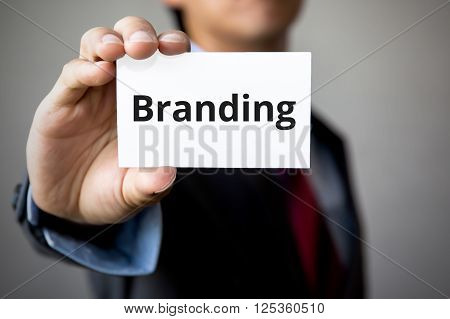 Businessman Presenting 'branding' Word On White Card