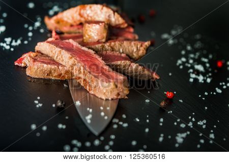 Medium rare steak slices on a knife on black plate with salt flakes and peppercorns