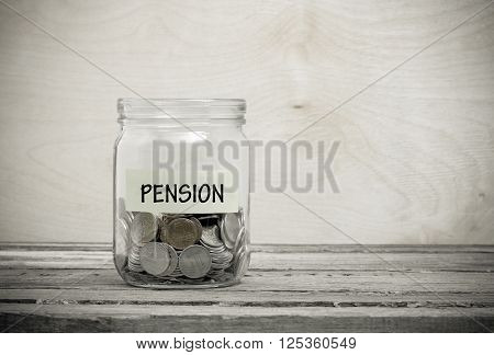 Label on a glass jar with the inscription - pension. Glass jar with coins. Financial concept on wooden background