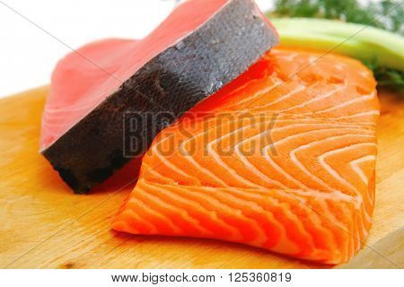 fresh raw salmon and red tuna fish pieces over wooden board isolated on white background