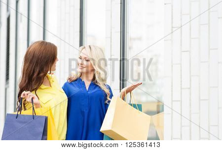 Two attractive young shopaholics with shopping bags outside. Blond pointing at clothes in store window.
