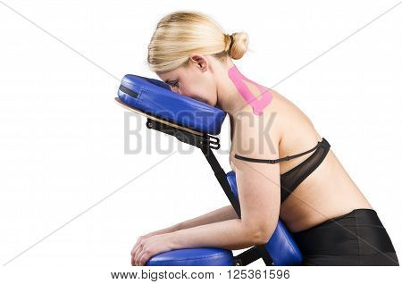 Patient In Massage Chair With Pink Kinesio Tape Over White Background.