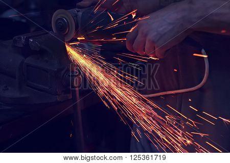 Angel grinder make flash sparks. Men's hand with grinder photo with toning