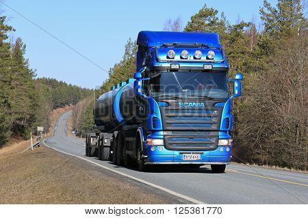 SALO, FINLAND - APRIL 10, 2016: Blue Scania R500 tank truck moves uphill on rural road at spring.
