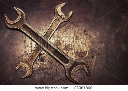two crossed dirty wrenches on grunge background top view with place for text