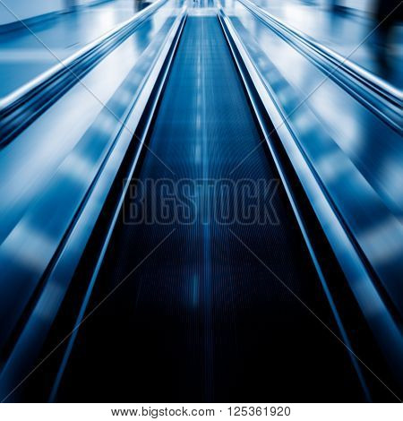 moving walkways at airport,blue toned image.