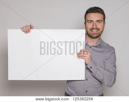 young man holding a white copyspace billboard on gray background