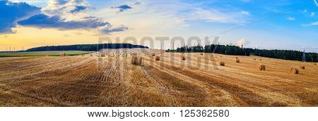 Hay bales on field. Autumn field with hay bales after harvest. Rural landscape with haystacks against the backdrop of a beautiful sunset sky. Panorama shot.