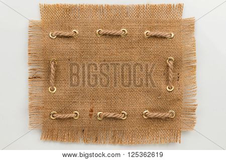 Frame made of burlap with a fringe and rope on a white background