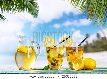 Glasses of summer ice tea drink on beach