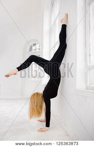 Sexy young yoga female doing handstand in white room against window in black sport suite