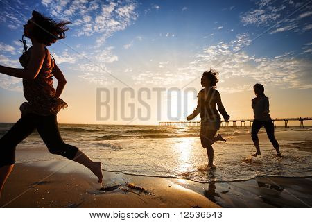 Three Girls Running By The Ocean At Sunset