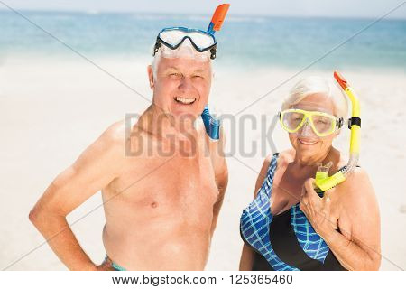 Senior couple wearing snorkel and diving goggles on a sunny day