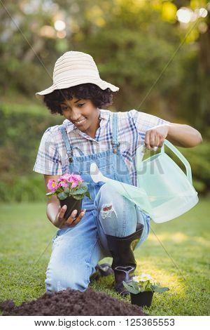 Smiling woman crouching in the garden watering flowers
