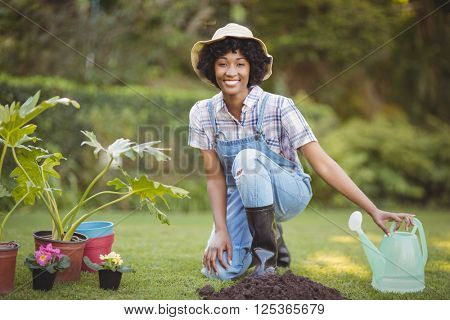 Smiling woman crouching in the garden looking at the camera