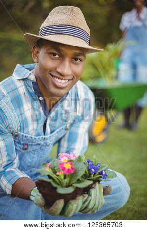 Handsome man crouching in the garden holding flowers