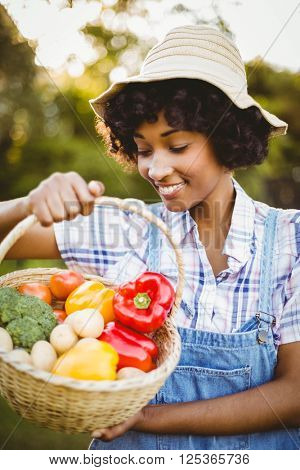 Smiling woman looking at basket of vegetables in the garden