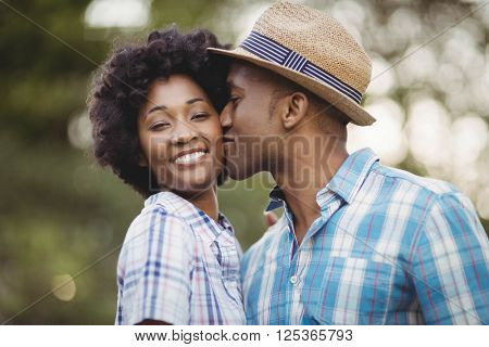 Smiling man kissing her girlfriends cheek in the garden