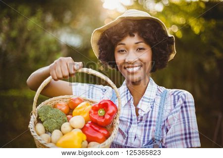 Smiling woman showing a basket of vegetables in the garden