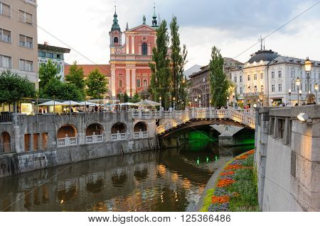 LJUBLJANA SLOVENIA - JULY 9 2009: Triple bridge and Ljubljanica river and riverbank with flowerbed